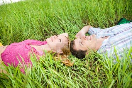 Photo pour Jeune couple d'amour étendu sur l'herbe verte à l'extérieur - image libre de droit