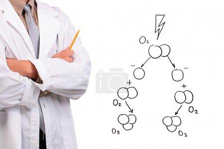 Photo pour Homme d'une blouse blanche, debout avec les bras croisés à côté d'un dessin de la formation de l'ozone. - image libre de droit