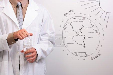 Photo pour Homme d'une blouse blanche, ouvrant une bouteille d'eau en se tenant debout à côté d'un dessin de la couche d'ozone. - image libre de droit