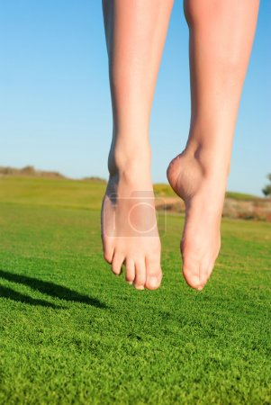 Closeup of feet of jumping on green field woman