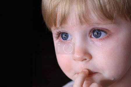 Photo for Portrait of a crying little child with big blue eyes. Close-up, the tears. - Royalty Free Image