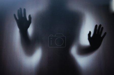 Photo pour Silhouette féminine photographiée à travers un verre sombre - image libre de droit