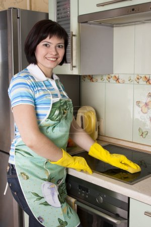 Photo for Young woman cleaning cooker at the kitchen. Smiling female washing stove top. - Royalty Free Image