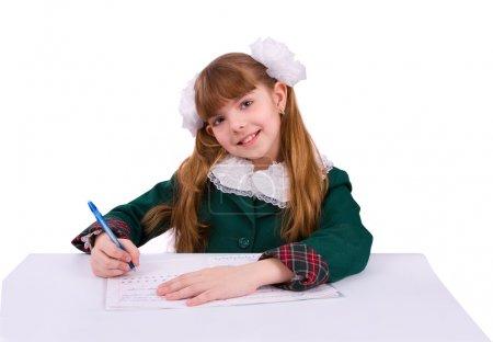 Photo pour Portrait d'une gentille petite fille dans sa classe, en train de passer un examen. Une heureuse écolière qui fait ses devoirs. Jeune étudiant écrivant . - image libre de droit