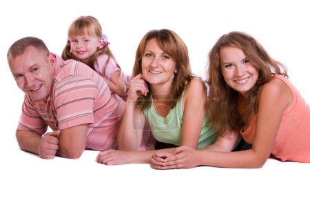 Photo pour Bonne famille. Mère, père et deux filles sourient. Femme, homme et filles sont couchés sur le sol et posant joyeusement sur fond blanc . - image libre de droit
