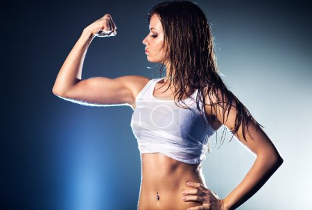Photo for Young strong sexy woman showing her muscles. - Royalty Free Image