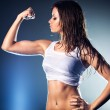 Young strong sexy woman showing her muscles....