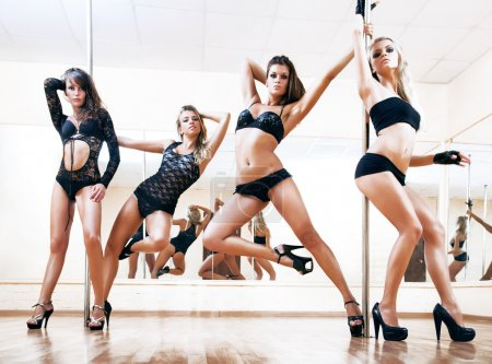 Photo for Four young sexy pole dance women. Bright white colors. - Royalty Free Image