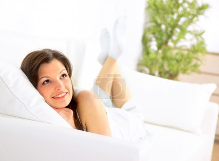 Photo pour Souriante fille couchée sur divan et pensant - image libre de droit