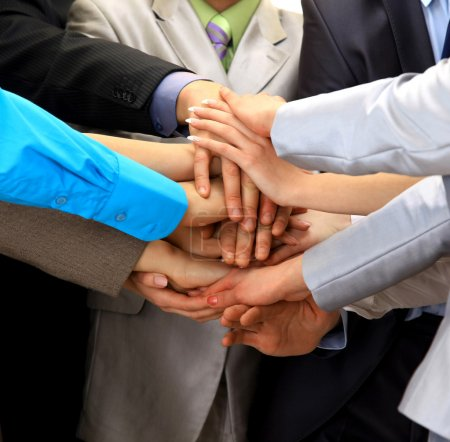 Group of business making a pile of hands in a light and modern offic