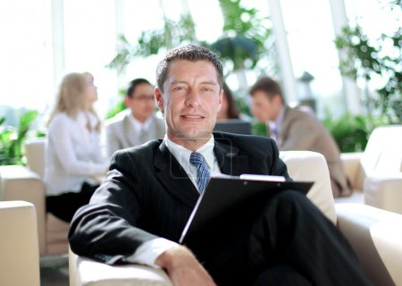 Happy business man with colleagues at a conference in the background