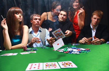 Stylish man in black suit folds two cards in casino poker at Las Vegas over