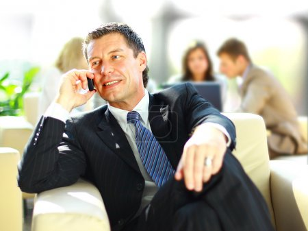 Concentrating businessman on call, coworkers talkling in background