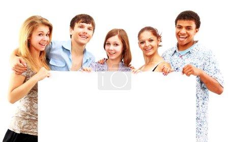 Photo pour Heureux groupe d'amis occasionnels tenant une bannière ajouter isolé sur blanc - image libre de droit