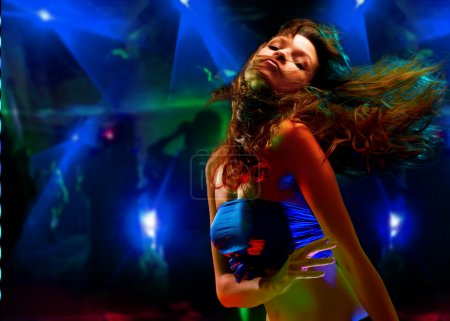Beautiful young woman dancing in the nightclub