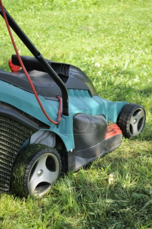 Photo for A lawn mower on a green lawn - Royalty Free Image