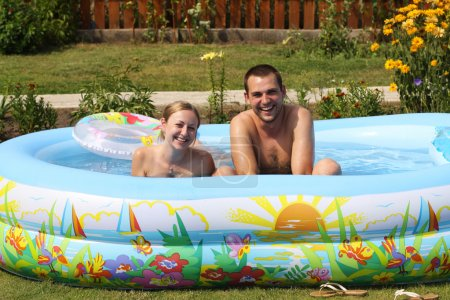 Young pair bathes in inflatable pool