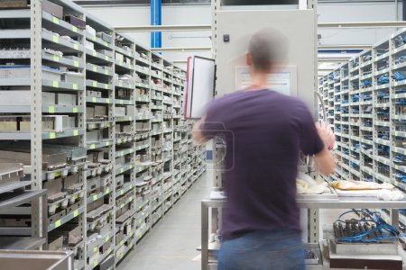 Photo pour Rayonnages métalliques avec pièces de longeron et technicien en mouvement, personne non reconnaissable - image libre de droit