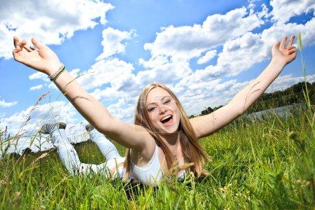 hübsches lächelndes Mädchen entspannt sich draußen im grünen Gras