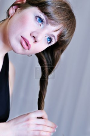 Photo pour Belle fille tortiller ses cheveux longs sur le gris - image libre de droit