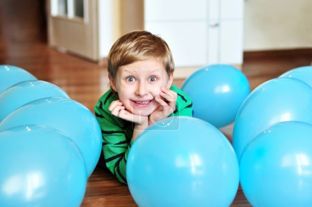 Boy laying with balloons