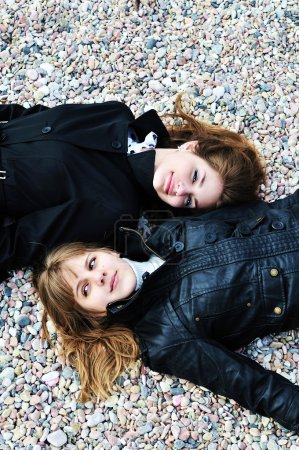 Two teen girls laying on the pebble