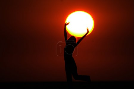 Photo for Girl with Sun in the hands on sundown - Royalty Free Image