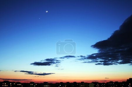 Photo pour Ciel bleu avec des nuages. coucher de soleil au-dessus des toits de maisons. - image libre de droit