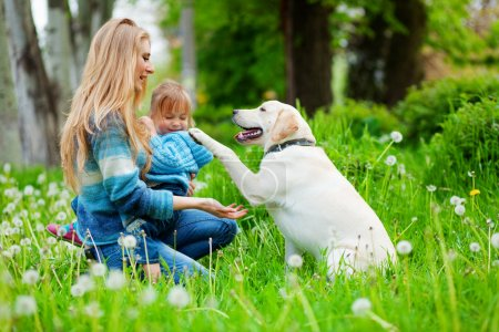 Photo for Beautiful woman with little girl and dog playing outdoors - Royalty Free Image