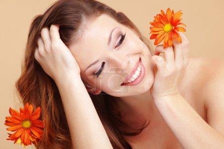 Photo for Studio portrait of beautiful smiling woman with flower - Royalty Free Image