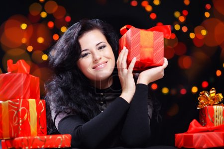 Photo for Cute woman with presents at night holiday celebration - Royalty Free Image