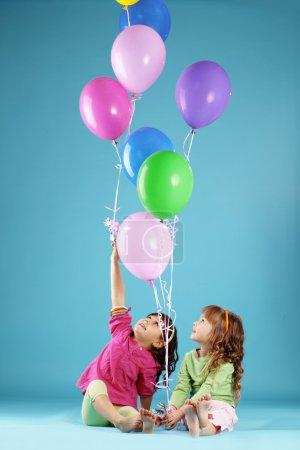 Foto de Niños felices con aire coloridos globos sobre azul - Imagen libre de derechos