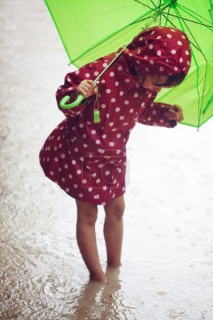 Photo for Little child walking in the rain - Royalty Free Image