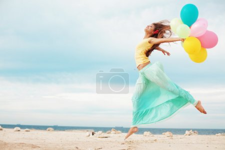 Photo for Happy girl holding bunch of colorful air balloons at the beach - Royalty Free Image