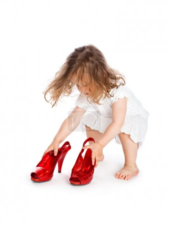 Little girl in white dress with big red shoes