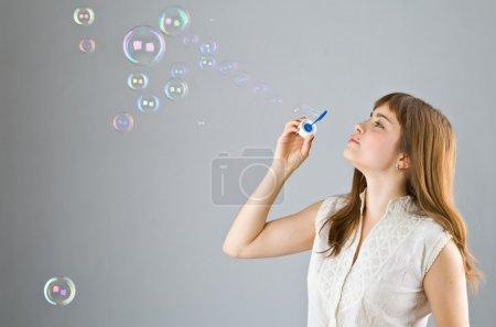 Young beautiful girl catch soap bubble
