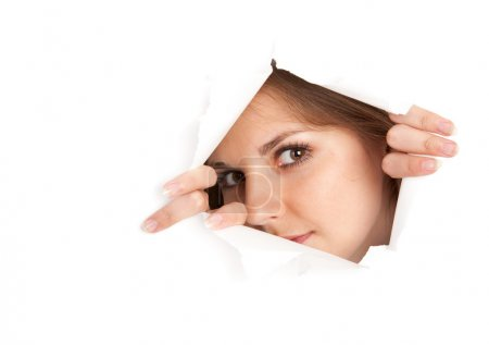 Foto de Una joven está mirando a través de una ventana hecha de papel. aislado sobre fondo blanco - Imagen libre de derechos