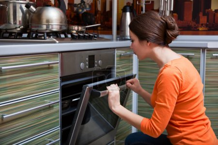 Photo pour Une belle jeune femme est la cuisson à la poêle - image libre de droit