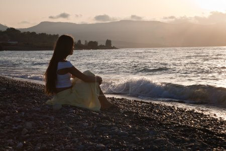 A woman is sitting on a beach