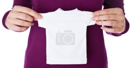 A woman is holding a small T-shirt in her hands