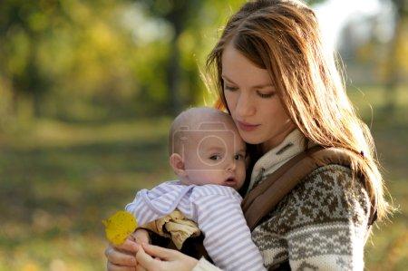 Photo pour Jeune mère avec son petit bébé dans un porte-bébé - image libre de droit