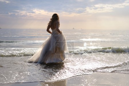 Photo for Bride walking along sea coast in the wedding dress - Royalty Free Image