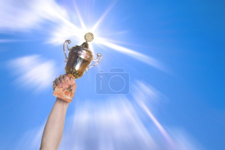 Photo for Hand of the person with a sports cup on a background of the bright sky. - Royalty Free Image
