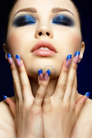 Photo for Close-up portrait of beautiful brunette with blue eye shadow make up and manicure - Royalty Free Image