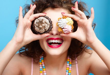 Photo for Portrait of beautiful curly brunette girl with two tarts - Royalty Free Image
