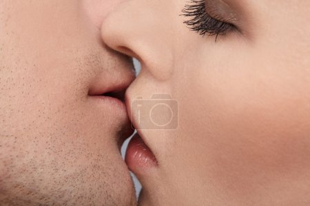 Close up portrait of young caucasian couple kissin...