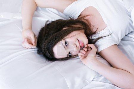 Photo pour Portrait de belle fille relaxant dans la chambre sur le linge - image libre de droit