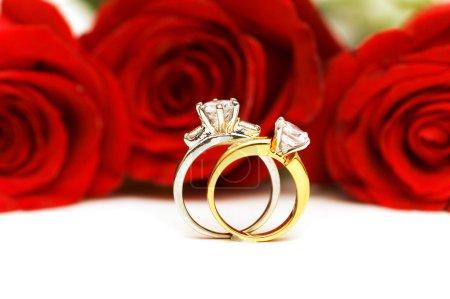 Photo pour Bagues en diamant et roses isolés sur le blanc - image libre de droit