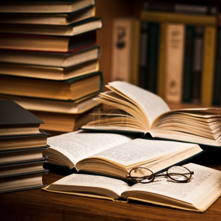 Photo for Opened book, lying on the bookshelf with a glasses - Royalty Free Image