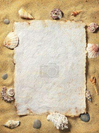 Sea shell, vintage paper on sand